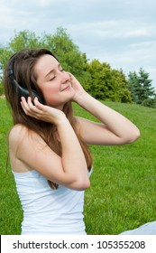 Girl in headphones listens to music in park.