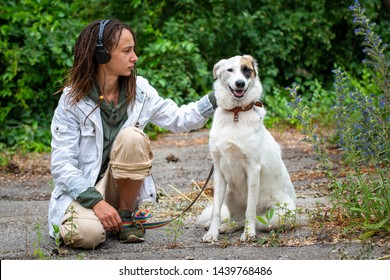 The girl in the headphones next to the dog pooch on the background of blurred green. Latino girl of appearance with dreadlocks wearing a white jacket. Summer day. Communication with the animal.