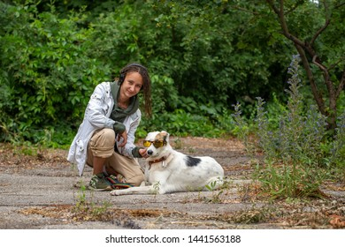 The girl in the headphones next to the dog pooch on the background of blurred green. Latino girl of appearance with dreadlocks. Communication with the animal. Fun photo. The dog