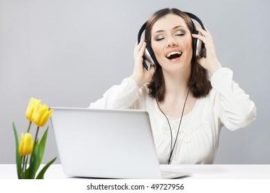 girl in headphones on the grey background
