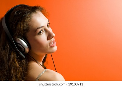girl in headphones on the orange background