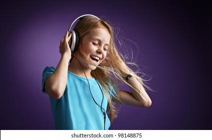 Girl with headphones on purple background