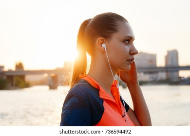 girl in headphones and sports uniform stands on the bridge background