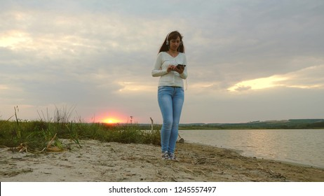 girl with headphones walking along beach with tablet and listening to music. girl in rays of sunset walking on beach and checking mail on tablet online