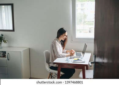 Girl in headphones works at the laptop in the home office and listens to music or a podcast.