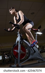 Girl in health club. Attractive Woman Spinning In The Fitness Club.