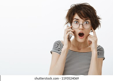 Girl hearing amazing and shocking news while talking on smartphone during repairment work in appartment. Portrait of stunned impressed attractive woman in round glasses covering one ear to hear better