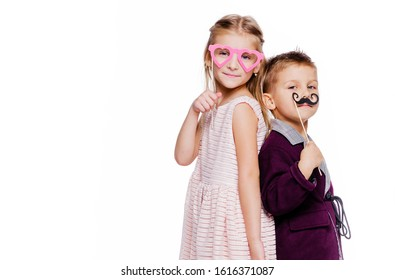 Girl with a heart-shaped cardboard glasses and a boy with a cardboard mustache posing on a white background