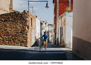 the girl in a helmet and bicycle uniform and white glasses goes with a mountain bike along an old street in Spain. Happy and smiling
