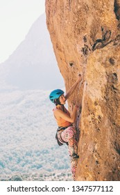 A girl in a helmet climbs a rock. Woman overcomes challenging climbing route on the background of beautiful mountains. Extreme hobby. Rock climbing in Turkey.