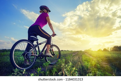 Girl in a helmet on a bicycle looks into the distance. A girl in a bicycle helmet and glasses looks at the bright sun at the end of the road. The concept of freedom and travel
