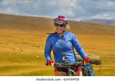 Girl in helmet, riding a bicycle with a large backpack for bicycling, along a dirt path in the desert, along a mountain river. Sunny day, high snowy mountains. Tien Shan, Kyrgyzstan, Asia