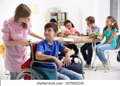 Girl helping boy in wheelchair at school