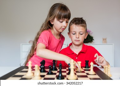 Girl helping boy while playing a game of chess on large chess board.
