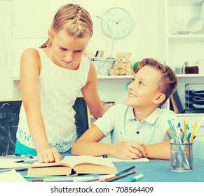 Girl is helping brother doing homework at home.