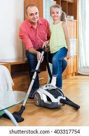 girl helping father to do regular clean-up indoors