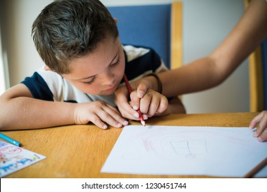 Girl helping her brother to draw