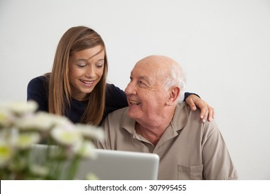 Girl helping to her grandfather with the computer