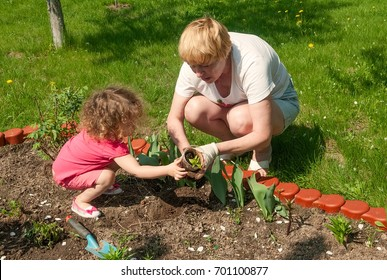 girl helping her granny in garden