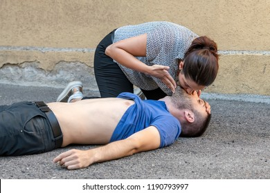 girl helping an unconscious guy with mouth to mouth resuscitation and cpr
