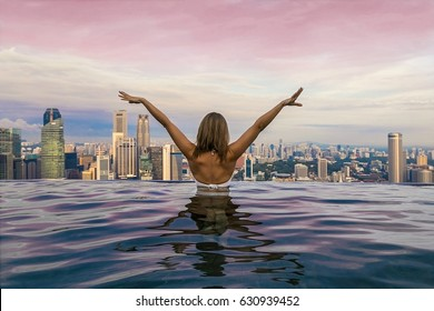 Girl with her back in the pool on the roof of a skyscraper