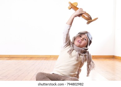 A girl in her bedroom, dressed as a pilot or aviator, plays with her wooden airplane as she dreams with open eyes and thinks about the future. Concept of: success, future, dreams and work.