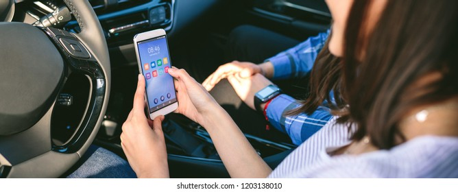 Girl with her boyfriend using the cell phone in the car