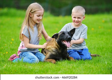 girl and her brother playing with dogs on grass