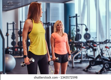 Girl with her coach trains with dumbbells in the modern gym. Health, diet, sport