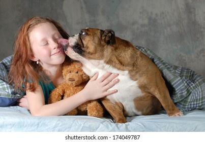 girl and her dog - pre teenage girl ready for cuddling with her dog - english bulldog
