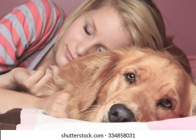 A Girl and her dog sleeping together on a bedroom.