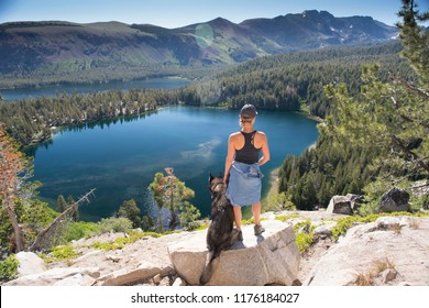 A girl and her dog stand above a beautiful high alpine lake on a sunny summer day in Mammoth, California.