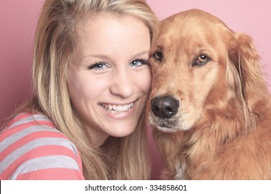 A Girl and her dog together on a bedroom with a pink wall.