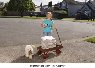 Girl with her dog and wagon delivering newspapers in her neighbourhood.