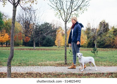 Girl and her dog walking in a autumn park