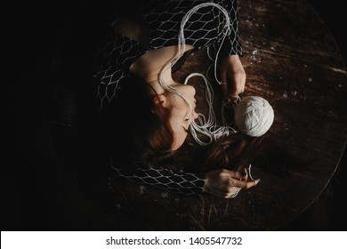 The girl with her eyes closed lies among the threads