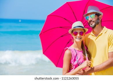 Girl and her father in sunglasses with an pink umbrella on the sandy beach