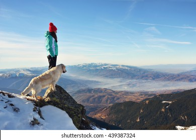 Girl with her golden retriever dog on top of a mountain during winter watching a beautiful landscape
