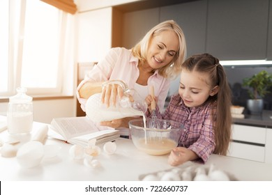A girl with her grandmother cooks a homemade cake. The grandmother pours milk into the dough. Next to them is a book of recipes