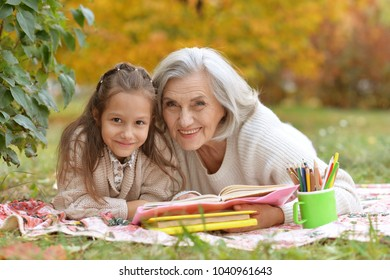 girl with her grandmother reading