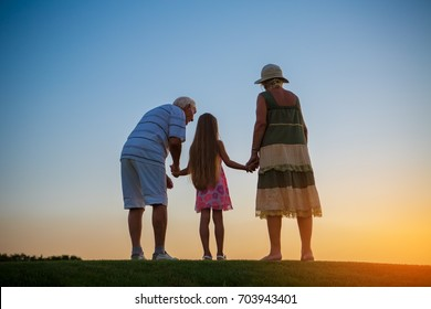 Girl and her grandparents. People standing on sunset background. Admiring the infinity.
