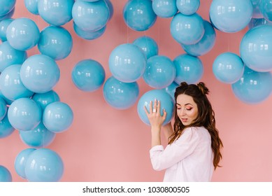 A girl with her hair in a pink shirt in a pink room with blue balls that hang from the ceiling