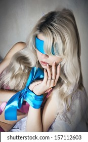 A girl with her hands tied and blindfolded
