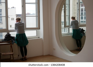 A girl and her mirror reflection standing at the window looking outside.