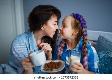 Girl with her mom having breakfast in the bed.