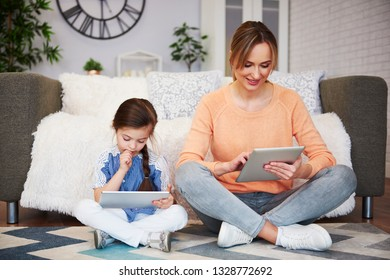 Girl and her mom using a tablet in living room