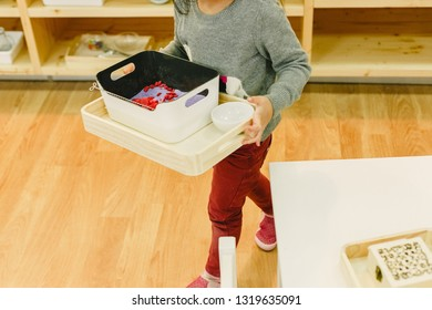 Girl in her montessori school moving trays with material from one shelf to another, concept of child autonomy.