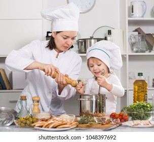 Girl and her mother are cooking soup together and adding spices in the kitchen at home.