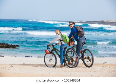 Girl with her mother having a weekend excursion on their bikes on a summer day in beautiful sea landscape