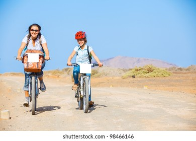 Girl with her mother having a weekend excursion on their bikes on a summer day in beautiful landscape